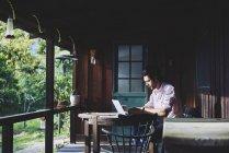 MID дорослий чоловік, використовуючи ноутбук на веранду, селективний фокус — стокове фото