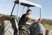 Mid adult woman on tractor, focus on foreground — Stock Photo