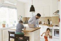 Средний взрослый мужчина и дети на домашней кухне, избирательный фокус — стоковое фото