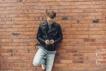 Adolescent garçon penché sur mur de briques, en utilisant smartphone — Photo de stock