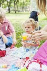 Mother giving daughter juice at birthday picnic — Stock Photo