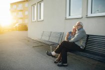 Seniorenpaar umarmt sich auf Bank, Fokus auf Vordergrund — Stockfoto