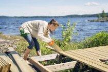 Mitte erwachsene Frau baut Deck vor See in Finnland — Stockfoto