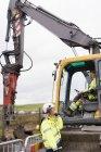 Femme parlant à l'homme à l'intérieur du déménageur de terre sur le chantier de construction — Photo de stock