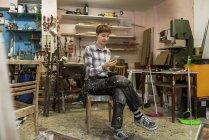 Carpinteiro usando telefone inteligente na oficina — Fotografia de Stock