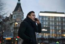 Jeune homme parlant sur un téléphone portable tout en marchant dans la rue de la ville — Photo de stock
