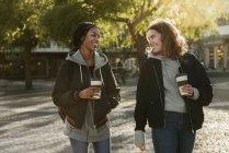 Meninas adolescentes sorridentes com xícaras de café — Fotografia de Stock