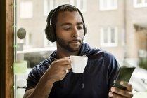 Молодий чоловік слухає музику в кафе, зосереджується на розбірливості. — стокове фото