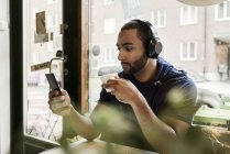 Giovane uomo che ascolta musica in un caffè, attenzione selettiva — Foto stock