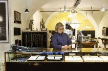Goldsmith using smart phone at counter of jewellery shop — Stock Photo