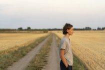 Teenage boy standing on rural road — Stock Photo