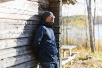 Hombre con gorro y chaqueta apoyados en la cabaña de madera - foto de stock
