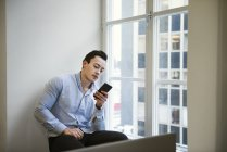 Young man using smart phone by window — Stock Photo