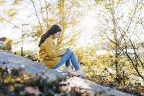 Chica vistiendo impermeable amarillo usando teléfono inteligente por los árboles - foto de stock