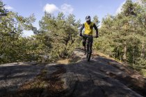 Man cycling through forest, selective focus — Stock Photo