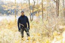 Homem usando jaqueta azul entre as árvores de outono — Fotografia de Stock