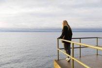 Молода жінка нахилилася над озером. — стокове фото
