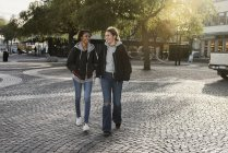 Teenage girls walking on cobblestone — Stock Photo