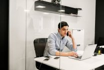 Jeune homme utilisant un ordinateur portable pendant qu'il parle au téléphone au bureau — Photo de stock