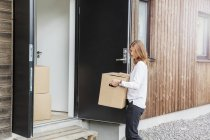 Woman carrying cardboard box into house — Stock Photo