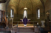 Priest in purple robes standing at chancel in church — Stock Photo