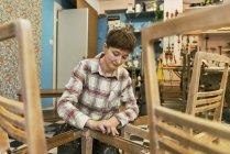 Carpenter sanding chair, selective focus — Stock Photo
