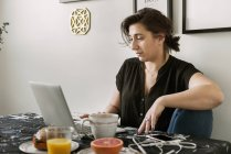 Young woman using laptop during breakfast — Stock Photo