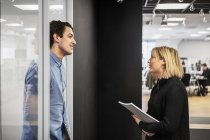 Coworkers talking in office, focus on foreground — Stock Photo