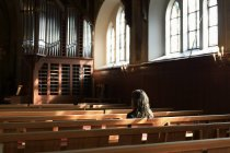 Priest sitting on pew in church, selective focus — Stock Photo