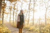 Mulher caminhando na floresta outonal — Fotografia de Stock