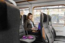 Mujer joven viajando en tren utilizando el ordenador portátil - foto de stock