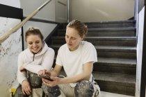 Peintres utilisant téléphone intelligent sur escalier appartement — Photo de stock