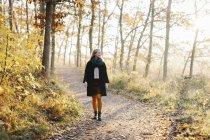 Donna che cammina nella foresta autunnale — Foto stock