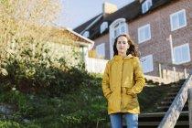 Дівчинка у жовтому плащі на сходах. — стокове фото