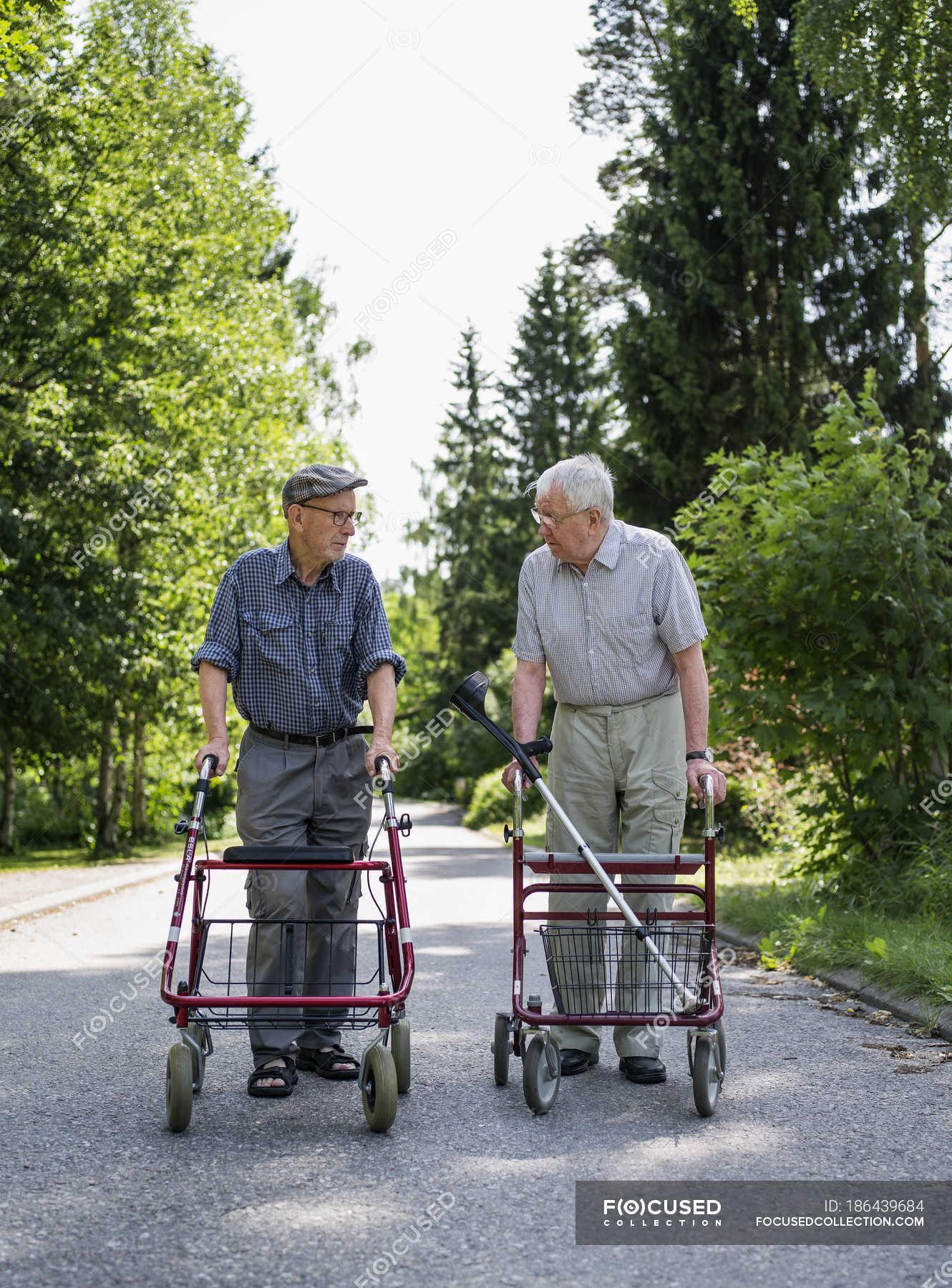 Two senior men with walking frames talking — Stock Photo | #186439684