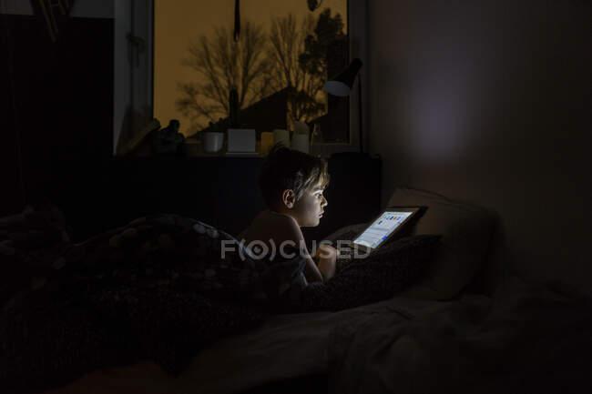 Мальчик играет с планшетным компьютером в постели по ночам — стоковое фото