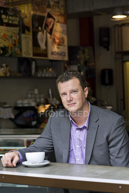 Portrait of businessman sitting in cafe and looking at camera — Stock Photo