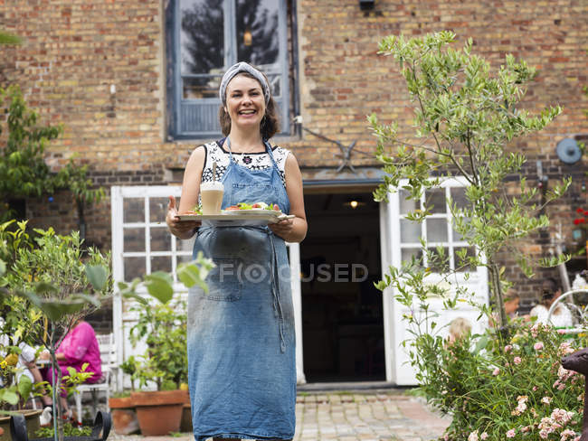 Портрет Жінка тримає підношення з їжею — стокове фото