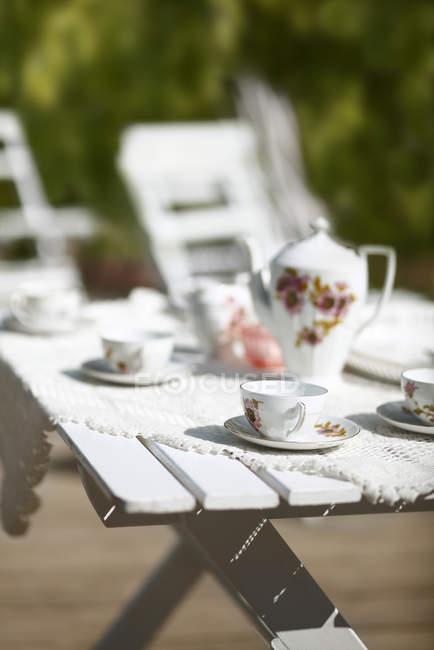Gartentisch mit Teekanne und Tassen serviert, im hellen Sonnenlicht — Stockfoto