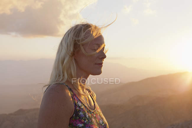 Female tourist relaxing in mountain landscape at sunset — Stock Photo