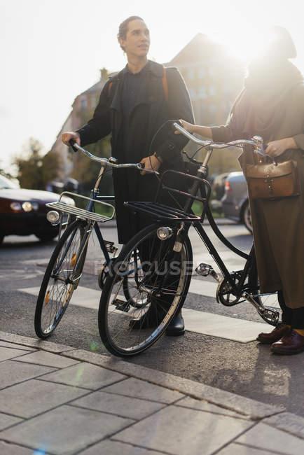 Два молодых человека, стоящие на велосипедах, вспышка объектива — стоковое фото