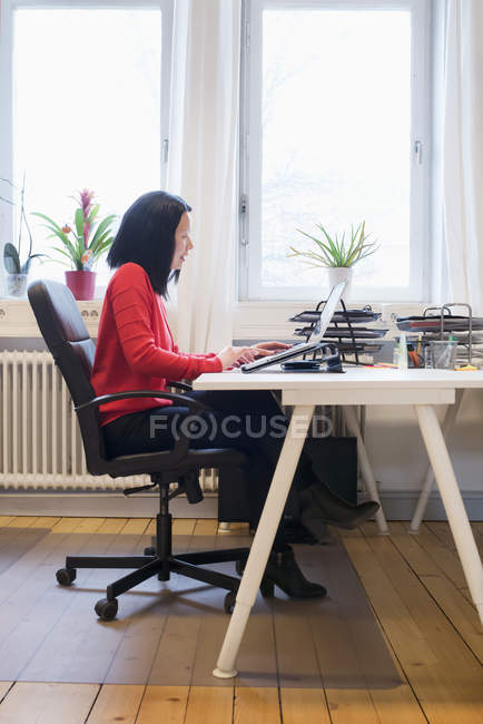 Mid-adult woman working on laptop indoors — Stock Photo
