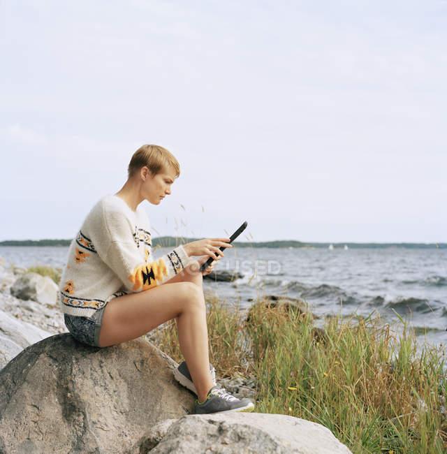 Жінка, використовуючи цифровий планшет на пляжі, зосередити увагу на передньому плані — стокове фото