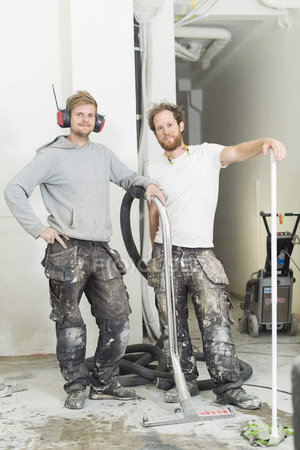Two men in protective workwear renovating house, selective focus — Stock Photo