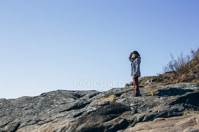 Woman standing and looking into distance on rocky beach — Fotografia de Stock