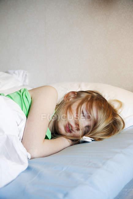 Дівчина лежав у ліжку з термометр, зосередити увагу на передньому плані — стокове фото