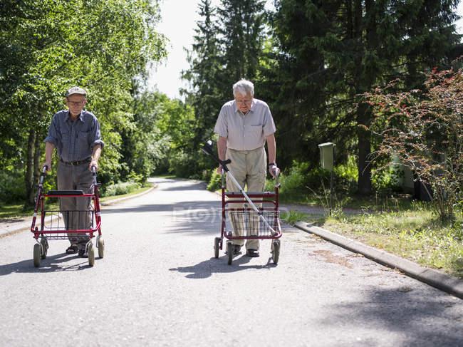 Two senior men walking with walking frames — Stock Photo