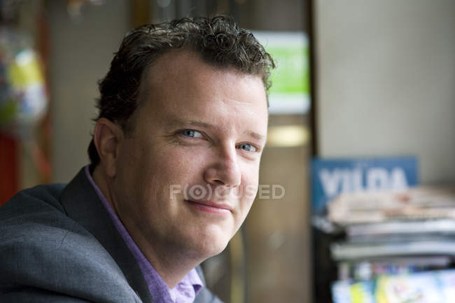 Portrait of businessman looking at camera, focus on foreground — Stock Photo