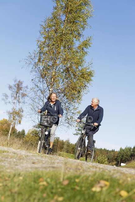 Senior homme et femme bicyclettes d'équitation — Photo de stock