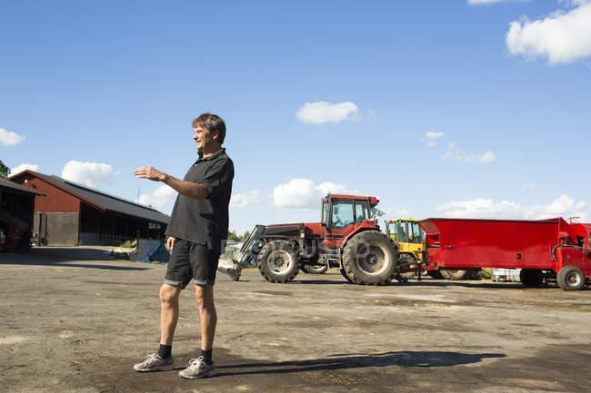Фермер стоїть у дворі ферми — стокове фото